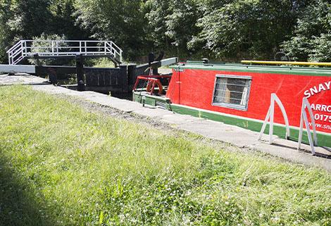 narrowboat by lock and footbridge